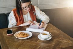 Woman is sitting in cafe at table, working. Girl fills out an application, signs documents, draws up resume. Royalty Free Stock Photography