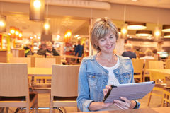 Woman sitting in the cafe using digital tablet Stock Photography