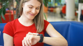 Woman sitting in cafe using her smartwatch, chatting with friends drinking cola from paper cup stock footage