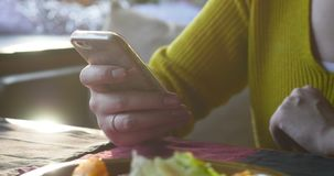 Woman in the cafe using smartphone while waiting. Woman sitting in the cafe and using smartphone while waiting an order stock video footage