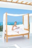 Woman sitting on a canopied day bed. Elegant happy woman sitting on a canopied day bed on an outdoor tropical patio smiling at the camera Stock Image