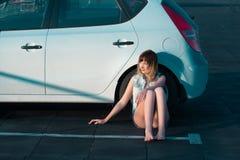Woman sitting beside car