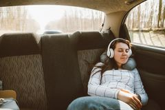 Woman sitting at car backseats and listening music. car travel c stock images
