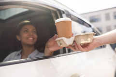 Woman sitting in car and buying coffee to go. Portrait of woman sitting in car and buying coffee to go Royalty Free Stock Photo