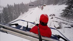 A woman   sitting on a car chairlift, during a snow storm stock video footage