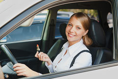 Woman sitting in the car and holding lipstick Stock Image