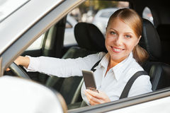 Woman sitting in the car and holding mobile phone Stock Image