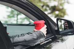 Woman sitting in the car with the phone and a cup of hot drink Royalty Free Stock Photos