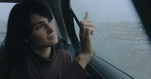 Woman sitting in a car at rainy day drawing heart on window. Woman sitting in a car at rainy day draws heart on misted window stock video