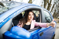 Woman sitting in the car and showing thumbs up on road Stock Image