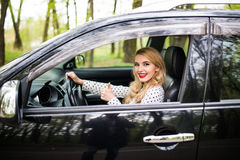 Woman sitting in the car and showing thumbs up on road Stock Images