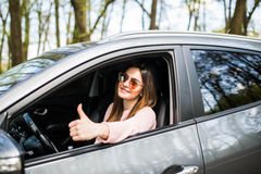 Woman sitting in the car and showing thumbs up in the street Stock Image