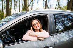 Woman sitting in the car and showing thumbs up in the street Royalty Free Stock Photo