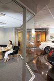 Woman sitting in car showroom office Stock Photography
