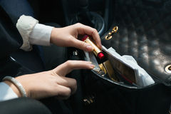 Woman sitting in car and taking lipstick out of handbag Royalty Free Stock Images