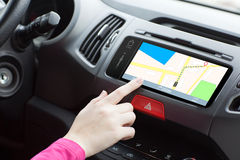 Woman sitting in a car and touch play finger in a navigation map Royalty Free Stock Photos