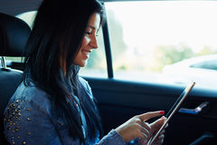 Woman sitting in the car and using digital tablet computer royalty free stock photos