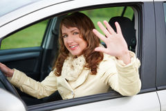 Woman sitting in the car and waving Stock Photos