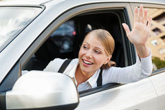 Woman sitting in the car and waving her hand Stock Image