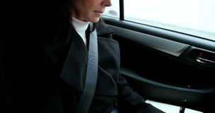 Woman sitting in car and writing on diary. Businesswoman sitting in car and writing on her diary stock video footage