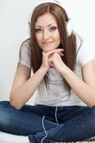 Woman sitting on carpet and listen to the music Royalty Free Stock Image