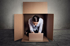 Woman sitting in carton box working on laptop computer. Closeup young businesswoman hiding sitting in the carton box working on laptop computer Royalty Free Stock Photo