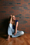 Woman sitting casually on floor Stock Images