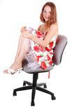 Woman sitting on chair. Lovely young woman in high heels sitting on a office chair in the studio with Stock Images