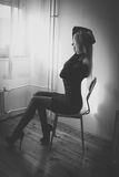 Woman sitting on chair. Blonde in dress and heels sitting on chair by the window royalty free stock images