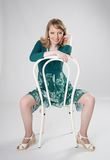 Woman sitting on a chair. Blonde in a green dress sitting on a white chair Royalty Free Stock Images