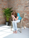 Woman sitting on the chair in depression Royalty Free Stock Photography
