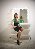 Woman sitting on chair at dressing room with mirror with bulbs Royalty Free Stock Photography