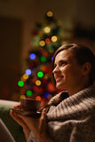 Woman sitting chair and drinking hot beverage. Thoughtful woman sitting chair and drinking hot beverage in front of Christmas tree Stock Photos