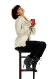 Woman sitting on chair enjoying a red cup Royalty Free Stock Photos