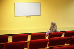 Woman sitting in chair in first row of hall Stock Image