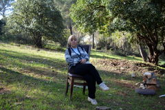 Woman sitting on a chair in the forest Stock Photos