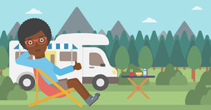 Woman sitting in chair in front of camper van. An african-american woman sitting in folding chair and giving thumb up on the background of camper van. Woman Royalty Free Stock Image