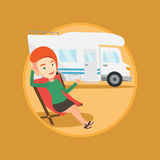 Woman sitting in chair in front of camper van. Stock Photo