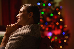 Woman sitting chair in front of Christmas tree. Thoughtful woman sitting chair in front of Christmas tree Royalty Free Stock Images
