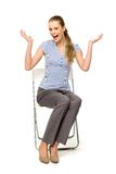 Woman sitting on chair gesturing Royalty Free Stock Photos