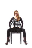 Woman sitting on a chair and holding hands on hips Royalty Free Stock Photo