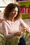 Woman Sitting In Chair Knitting Stock Image