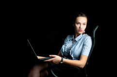 Woman sitting on a chair with a laptop in hand. Stock Photos