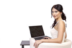 Woman sitting in a chair with a laptop. Young beautiful woman sitting in a chair with a laptop Royalty Free Stock Photography