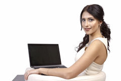 Woman sitting in a chair with a laptop. Young beautiful woman sitting in a chair with a laptop Stock Image