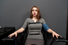 Woman sitting on chair during lie detector test. Front view of frightened woman sitting on chair while lie detector measuring pulse. Female adult with indicators royalty free stock images