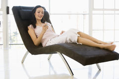 Woman sitting in chair listening to MP3 player Royalty Free Stock Image
