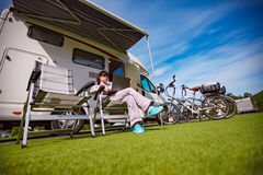 Woman sitting on a chair near the camper and looking at a laptop. Caravan car Vacation. Family vacation travel, holiday trip in motorhome Stock Photography