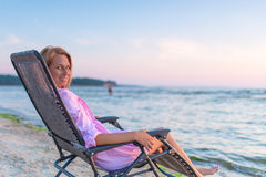Woman sitting in chair near a ocean Stock Photography