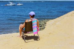 Woman sitting on an chair by the ocean and looking into the distance in the sunlight. Blonde woman sitting on an chair by the ocean and looking into the distance royalty free stock photography